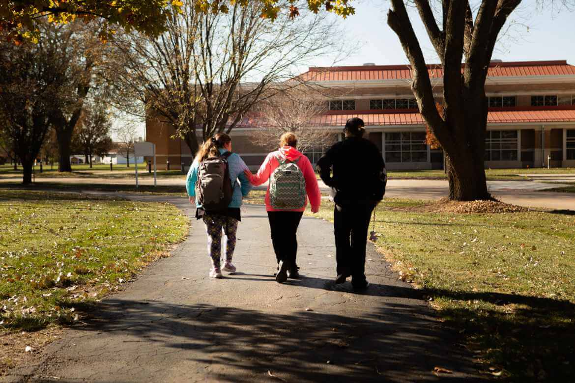 Three students walking together away from the camera on school grounds.